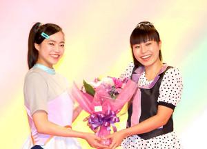 卒業する上原りさ(右)に花束を渡す秋元杏月