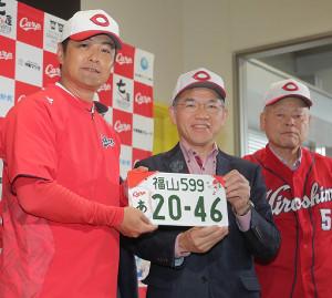 福山市・枝広市長(真ん中)から広島・緒方監督(左)に広島とコラボした図柄入りの福山ナンバーが贈られた