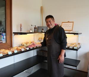 自慢のパンを紹介する憲史さん、後ろのバットは中村紀洋さんのもの