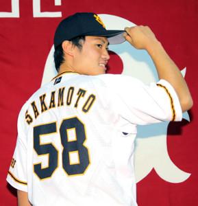 会見で新しい背番号「58」のユニホームを披露した坂本工