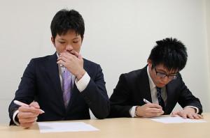 四段昇段を果たし、万感の思いの中で調査書を記入する出口若武三段(左)と黒田堯之三段