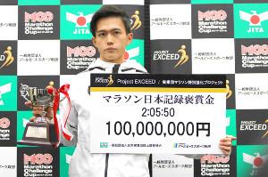 1億円の褒賞金ボードと記念カップを手にする大迫傑(カメラ・太田 涼)