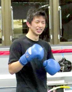 ミット打ちの合間に笑顔を見せる田口良一
