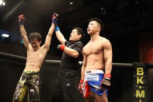 勝ち名乗りを受ける鮎田直人(左)と、敗戦に呆然とする藤田大和(右)