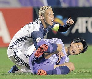前半、広島・東(手前)と競り合い倒れた本田