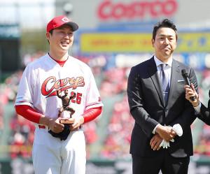 黒田博樹氏から贈呈品を受けとり、笑顔をみせる新井貴浩氏