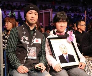 祖父・健裕さんの遺影を手にリングサイドで観戦する田中恒成の兄・亮明さん(左)と妹の杏奈さん(カメラ・谷口 健二)