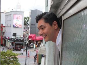 浅草演芸ホールから外を眺める昔昔亭A太郎(カメラ・越川 亘)