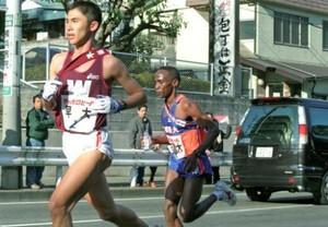 第77回東京箱根間往復大学駅伝競走第1日。2区で8人抜きの快走を見せた平成国際大のジョン・カーニー(右)。左は早大・森村哲。2001年1月2日