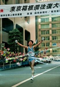 第71回東京箱根間往復大学駅伝競走・最終日。山梨学院大のアンカー・瀬戸優之が両手をあげ歓喜の優勝ゴール。山梨学院大はV2を達成した。東京・千代田区の読売新聞社前で。1995年1月3日