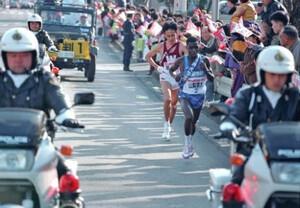 第70回東京箱根間往復大学駅伝競走第1日。2区、早大・花田勝彦(左後ろ)がトップでタスキを引き継ぐも腹痛を起こし、山梨学院大のエース、ステファン・マヤカ(右手前)に10キロ付近で抜かれる。山梨学院大は2分以上の差をつけ独走態勢に。神奈川・横浜市で。1994年1月2日