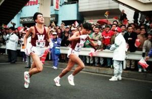 第69回東京箱根間往復大学駅伝競争第1日。往路1区、過去に2回もおこしたブレーキの悪夢を完全に振り払う快走を見せた早大・櫛部静二(左)。区間新で2区の渡辺康幸(右)にトップでタスキを渡す。鶴見中継所で。1993年1月2日