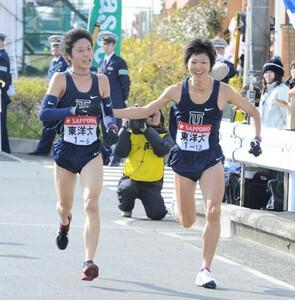 ◆第86回箱根駅伝・復路(3日)東洋大、9区工藤へ笑顔でタスキを託す8区千葉(左)