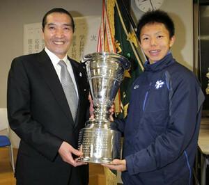 箱根駅伝で30年ぶりの総合優勝を果たした祝勝会が3日、行われ優勝杯を手に笑顔を見せる日体大・服部翔大主将(右)と松浪健四郎理事長。大学側から「海外高地合宿」がプレゼントされることになった。横浜市の日本体育大学健志台キャンパスで。