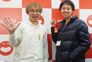 手のひらを見せるアポロン山崎(左)とハートプラスマークを手にする小林春彦