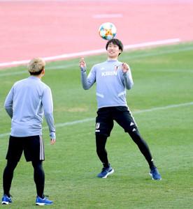 ボール回しの練習で汗を流す鎌田(右)