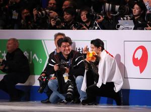 ネーサン・チェンのフォトセッションの際にカメラマンの横に並んでカメラを構える真似をする羽生結弦(カメラ・矢口 亨)