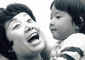 長男の加藤和也さんを抱っこし笑顔のひばりさん(74年)