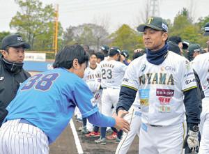 試合前に握手する二岡監督(右)と武田監督