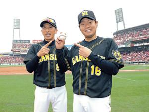 矢野監督(左)に祝福されウィニングボールを手にする西