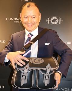 自身が監修した日本限定発売のハンティングワールドのバッグを手に笑顔で撮影に応じるエディー氏