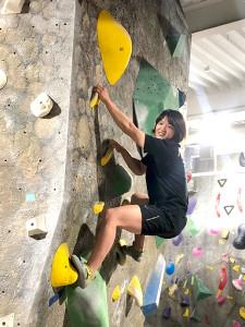 ボルダリングの壁を登る新井千鶴