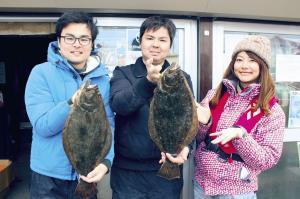 ヒラメを釣った長嶺共吾さん(中)と杉山茂輝さん(左)を祝福する由梨ちゃん(ちがさき丸で)