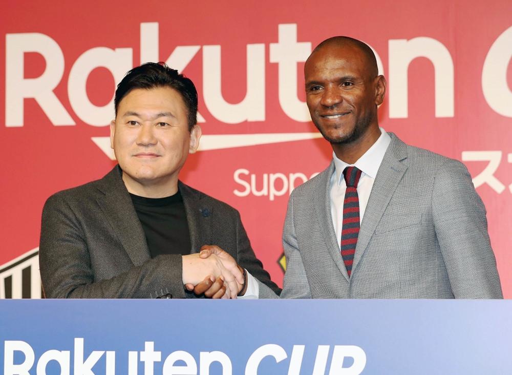 握手する神戸・三木谷オーナーとバルセロナのアビダル氏