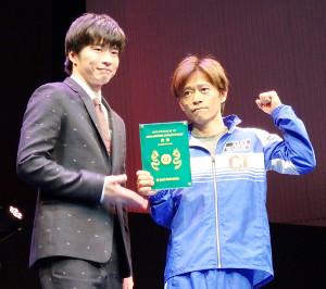 優勝の今垣光太郎は俳優の田中圭から記念の純金メダル盾を贈られた
