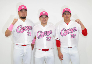 「ピンクリボンユニホーム」を披露する(左から)中崎、会沢、野間