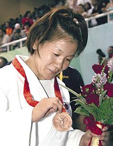 北京五輪で銅メダルを獲得し、メダルを見つめる谷