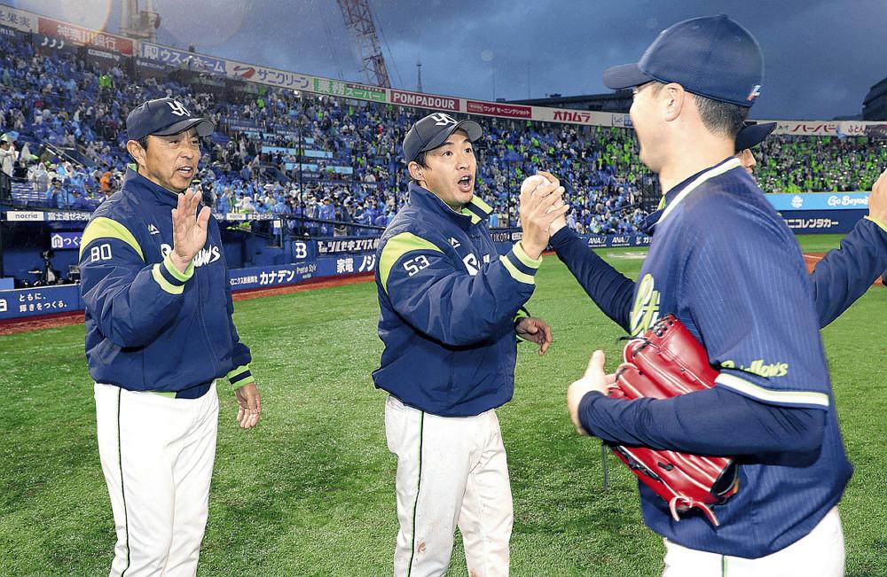 5勝目を挙げた五十嵐は、最後を締めた石山(右)からウィニングボールを受け取る(左は小川監督=カメラ・関口 俊明)
