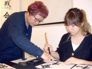 篠崎先生(右)の指導を受けながら真剣な表情で筆を動かす大橋