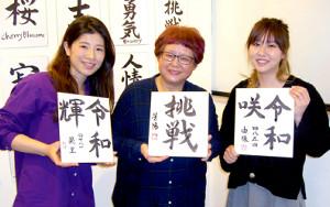 大橋(右)と仲良しの西舘(左)も書道体験に参加。色紙を持って篠崎先生(中央)と記念撮影