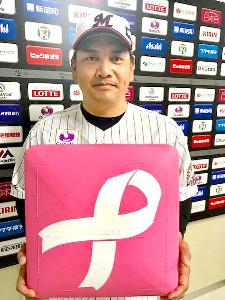 井口監督はピンクリボンがデザインされたピンクのベースを手にする