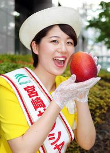 宮崎のPRに来社し、特産品のマンゴーを手に笑顔を見せる宮崎サンシャインレディの今井千尋さ