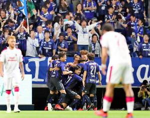 今季ホーム初勝利を挙げ、ガッツポーズするG大阪・宮本監督(左はC大阪・ロティーナ監督)