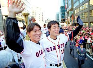 2002年、日本一となった巨人が優勝パレード。パレードカーの車上から手を振って沿道のファンに応える、巨人・松井秀喜(左)と上原浩治(右)