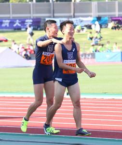 男子100メートルで優勝した東洋大・宮本(右)はチームメートから祝福され笑顔を見せた
