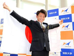 南米選手権の日本代表に選出され、笑顔で日の丸を掲げる法大・上田綺世(カメラ・宮崎 亮太)