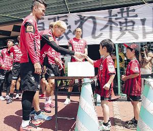 「頑張れ横山」と書かれた横断幕の前で募金活動を行う札幌の選手たち