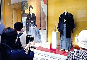 国民栄誉賞授与式で着用した羽生家の家紋入りの紋付きはかま「仙台平」の前で多くの人が足を止める