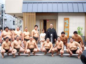 鳴戸親方夫妻と12人の弟子が新しい部屋の前で記念撮影