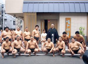 鳴戸親方夫妻と12人の弟子が新しい部屋の前で記念撮影した