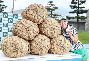 優勝副賞のコシヒカリ米俵6俵を贈られ笑顔を見せる上田桃子