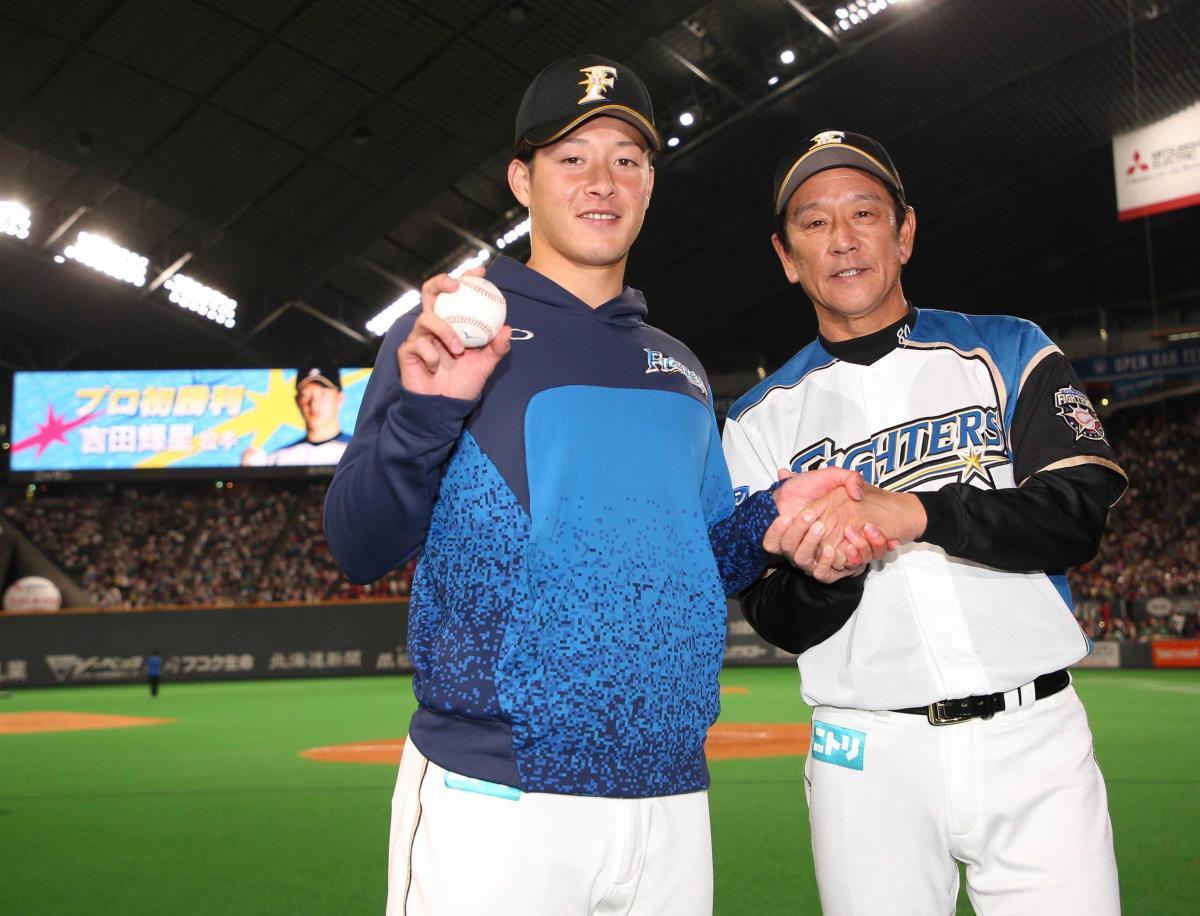 プロ初勝利を上げウイニングボールを手に栗山監督(右)と握手をする吉田輝星