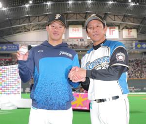 プロ初登板初勝利を挙げウイニングボールを手にする吉田輝星(左)を祝福する栗山英樹監督