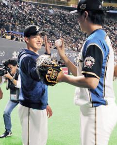 プロ初登板初勝利を挙げた吉田輝(左)は、セーブの石川直からウィニングボールを笑顔で受け取った(カメラ・池内 雅彦)
