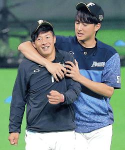 プロ初勝利から一夜明け、セーブを挙げた石川直(右)とじゃれ合う吉田輝