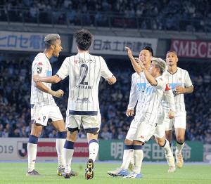 先制点を決めた札幌・鈴木(左)を迎え入れる選手たち